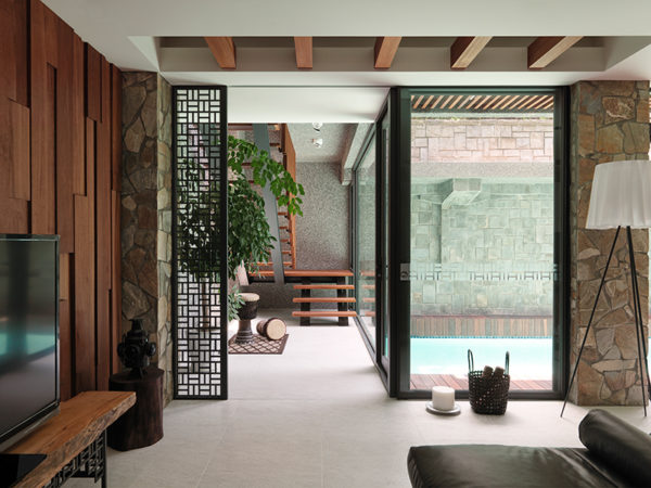Water reflects off the basement-level pool, flooding a once dark downstairs space with natural light. Left The far wall of the basement level, which backs onto the hillside, is finished with ceramic tile to protect from the soil behind it. The TV stand and back wall are custom designed by Ryan Kuo from teak.