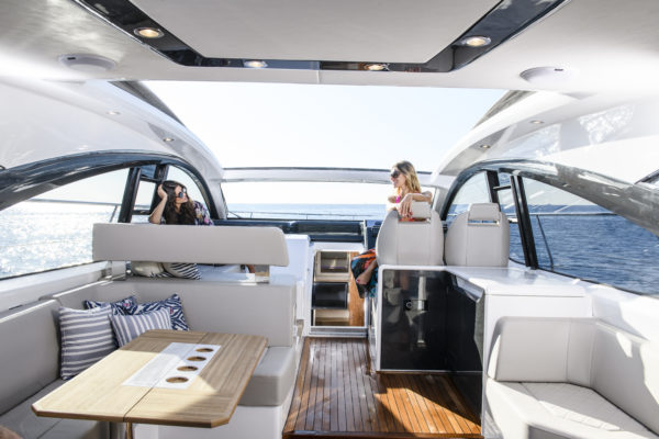 The interior features seating around a dining table, and a sofa by the helm