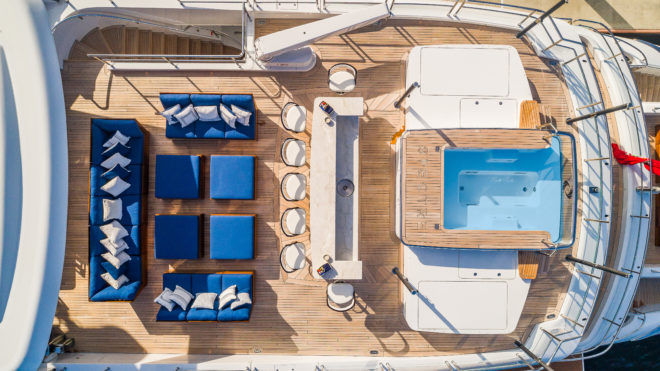 The stunning sundeck / bridge deck includes a comfortable lounge area, an aft-facing bar (also pictured bottom left) and a rectangular spa pool