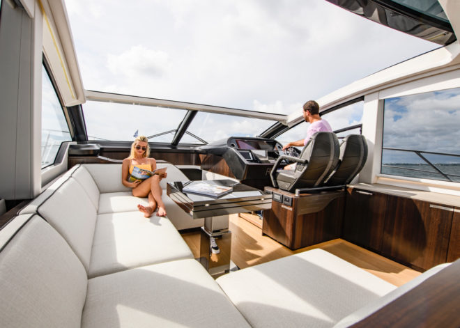 The saloon has white sofas, a black foldout table and a helm with leather bucket seats