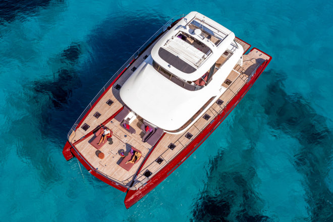 The red-hulled Lagoon Sixty 7 powercat features in REVIEWS; Photo: Nicolas Claris