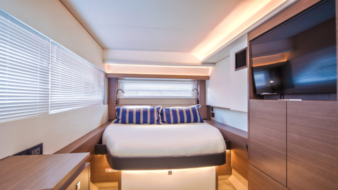 The master suite features a forward-facing bed towards the aft end of the starboard hull, separated from the engine compartment