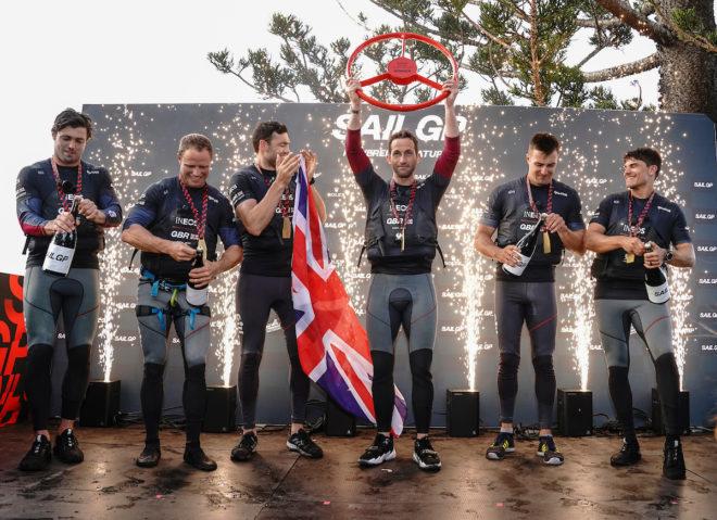 On his event debut, Great Britain helmsman Sir Ben Ainslie (with trophy) celebrates victory at the SailGP Sydney with Iain Jensen, Luke Parkinson, Matt Gotrel, Neil Hunter and Richard Mason